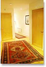 corridor with antique Kazak and antique Baluch long rugs